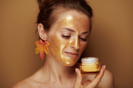 Portrait of middle age woman with golden cosmetic face mask and autumn leaf earring enjoying fragrance of cosmetic product on brown background.