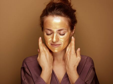 Portrait of relaxed young woman with golden cosmetic face mask isolated on beige background. Stock Photo