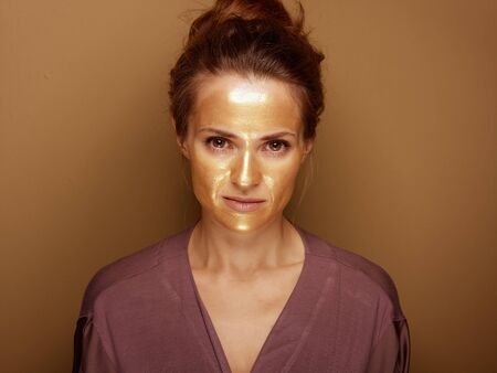 Portrait of modern housewife with golden cosmetic face mask isolated on beige.
