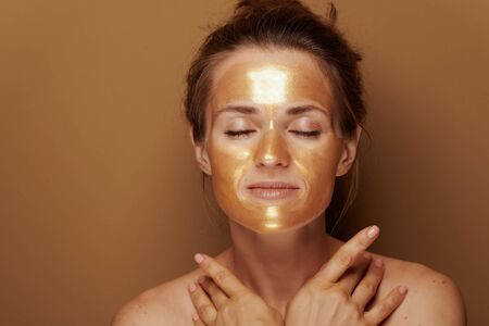 Portrait of relaxed young housewife with golden cosmetic face mask on bronze background.