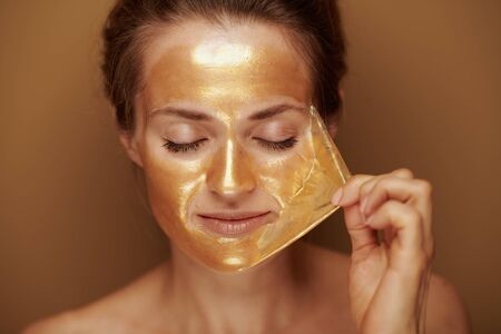 Portrait of modern woman removing golden cosmetic face mask against beige background.