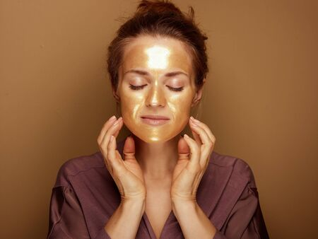 Portrait of elegant housewife with golden cosmetic face mask making facial self massage on brown background.