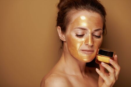 Portrait of 40 year old woman with golden cosmetic face mask holding cosmetic product jar isolated on beige. Stock Photo