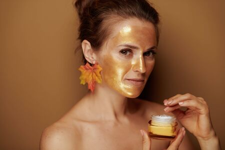 Portrait of modern 40 year old woman with golden cosmetic face mask and autumn leaf earring using cosmetic product against brown background.