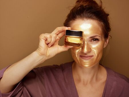Portrait of smiling modern 40 year old woman with golden cosmetic face mask showing cosmetic product jar against brown background.