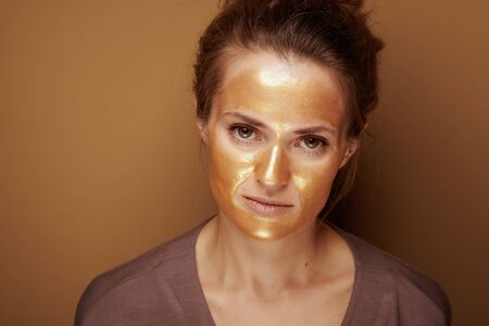 Portrait of elegant woman with golden cosmetic face mask isolated on bronze background.