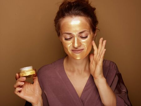 Portrait of relaxed modern woman with golden cosmetic face mask holding cosmetic product jar and touching face isolated on beige.