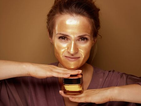 Portrait of modern housewife with golden cosmetic face mask holding cosmetic product jar isolated on beige background.