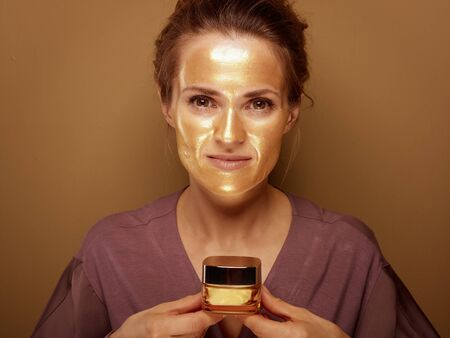 Portrait of elegant 40 year old woman with golden cosmetic face mask holding bottle of facial creme against bronze background.