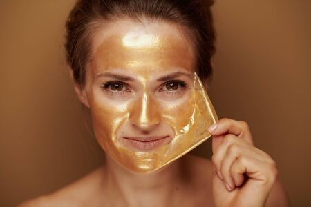 Portrait of elegant housewife removing golden cosmetic face mask isolated on bronze background.