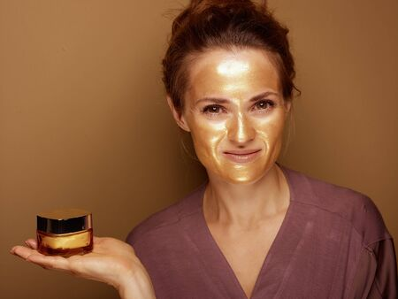 Portrait of smiling modern woman with golden cosmetic face mask showing bottle of facial creme against brown background.