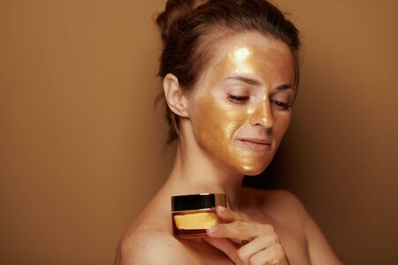 Portrait of modern middle age woman with golden cosmetic face mask holding bottle of face creme isolated on bronze background.