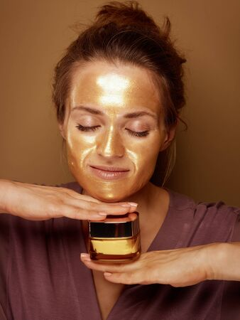 Portrait of relaxed elegant middle age woman with golden cosmetic face mask holding bottle of face creme against bronze background. Stock Photo