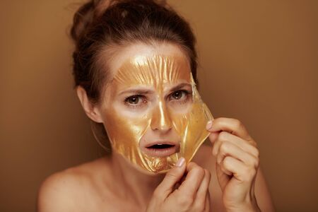 Portrait of shocked elegant 40 year old woman removing golden cosmetic face mask isolated on beige background.