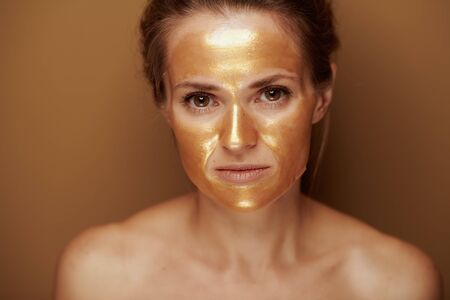 Portrait of young housewife with golden cosmetic face mask isolated on beige. Stock Photo