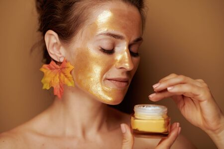 young woman with golden cosmetic face mask and autumn leaf earring using cosmetic product against brown background.