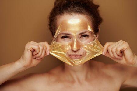 Portrait of cheerful modern 40 year old woman removing golden cosmetic face mask isolated on brown background.