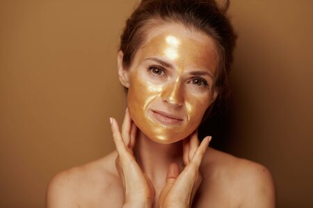 Portrait of relaxed young woman with golden cosmetic face mask on brown background.