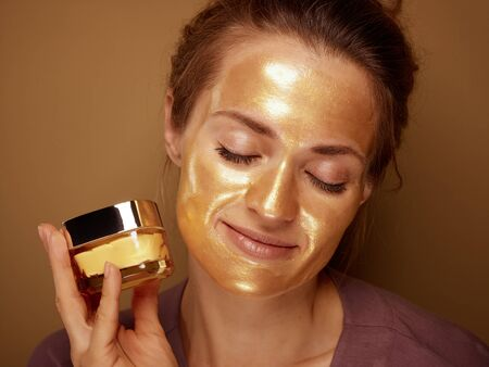 Portrait of relaxed modern woman with golden cosmetic face mask holding bottle of face creme isolated on beige.