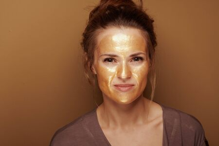 Portrait of modern woman with golden cosmetic face mask against bronze background.