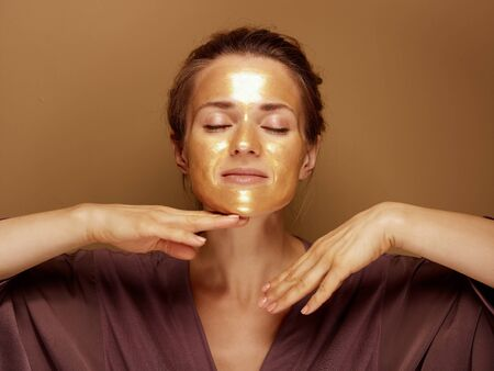Portrait of relaxed elegant woman with golden cosmetic face mask making facial massage against beige background.