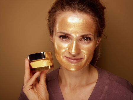 Portrait of smiling middle age woman with golden cosmetic face mask showing cosmetic product jar against bronze background. Stock Photo