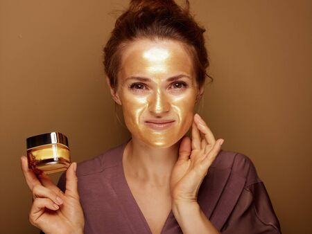 Portrait of smiling elegant 40 year old woman with golden cosmetic face mask holding bottle of face creme and touching face against brown background.