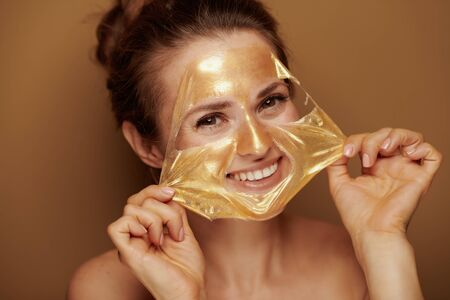 Portrait of cheerful young woman removing golden cosmetic face mask on bronze background.