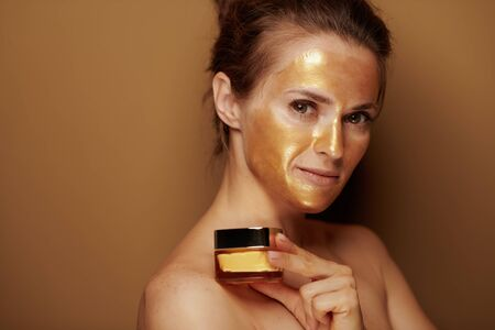 Portrait of modern woman with golden cosmetic face mask holding cosmetic product jar isolated on bronze background. Stock Photo