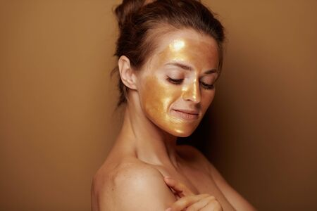 Portrait of modern middle age woman with golden cosmetic face mask on bronze background. Stock Photo