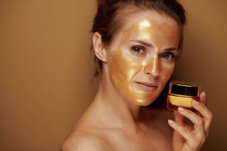 Portrait of elegant housewife with golden cosmetic face mask holding cosmetic product jar on bronze background. Stock Photo