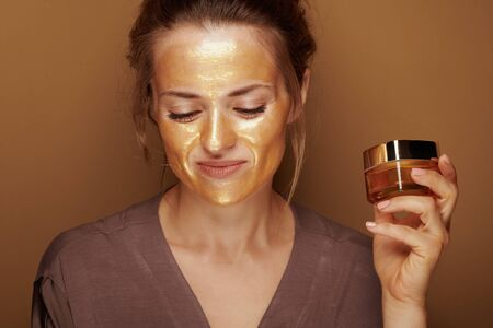 Portrait of happy elegant woman with golden cosmetic face mask holding facial creme jar isolated on bronze background.
