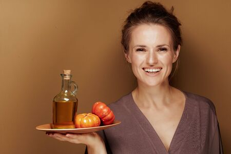 Hello autumn. Portrait of happy elegant 40 year old woman in a bathrobe showing pumpkin oil against bronze background.