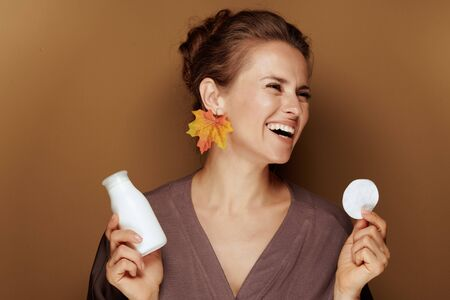 Hello autumn. smiling middle age woman in a bathrobe with autumn leaf earring holding face cleansing milk and cotton swab on brown background. Stock Photo