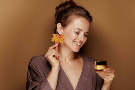 Hello autumn. happy young woman in a bathrobe with autumn leaf earring looking at facial creme isolated on beige.