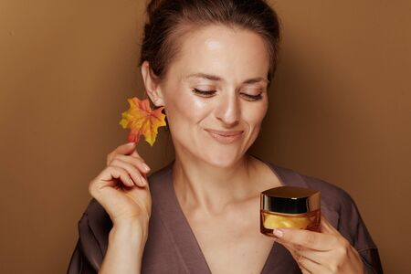 Hello autumn. Portrait of smiling modern woman in a bathrobe with autumn leaf earring looking at facial creme isolated on bronze background.