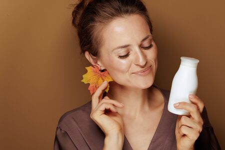 Hello autumn. happy elegant 40 year old woman in a bathrobe with autumn leaf earring and face cleansing milk on bronze background.