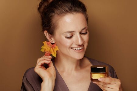 Hello autumn. happy modern 40 year old woman in a bathrobe with autumn leaf earring looking at facial creme on bronze background. Stock Photo