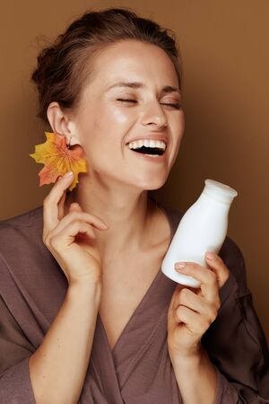 Hello autumn. smiling elegant woman in a bathrobe with autumn leaf earring and face cleansing milk isolated on beige.