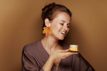 Hello autumn. Portrait of smiling elegant woman in a bathrobe with autumn leaf earring enjoy fragrance of facial creme against brown background.