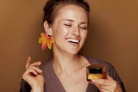 Hello autumn. Portrait of smiling young woman in a bathrobe with autumn leaf earring holding facial creme on beige background.