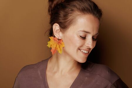 Hello autumn. smiling elegant 40 year old woman in a bathrobe with autumn leaf earring on brown background.