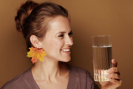 Hello autumn. Portrait of smiling middle age woman in a bathrobe with autumn leaf earring looking at glass of water against brown background.
