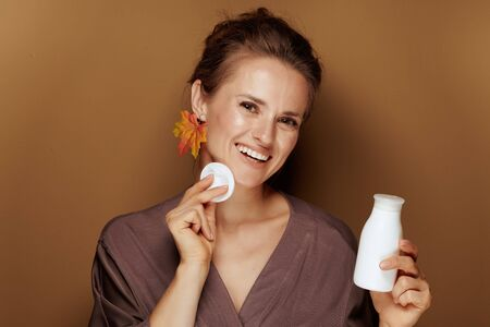 Hello autumn. Portrait of smiling modern woman in a bathrobe with autumn leaf earring using face cleansing milk and cotton swab against beige background. Stock Photo