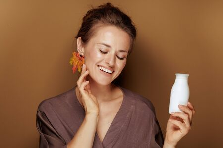 Hello autumn. Portrait of smiling elegant middle age woman in a bathrobe with autumn leaf earring holding face cleansing milk against bronze background. Stock Photo
