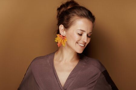 Hello autumn. Portrait of happy young woman in a bathrobe with autumn leaf earring isolated on beige background.