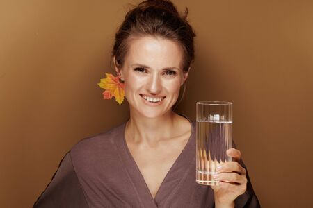 Hello autumn. Portrait of happy elegant woman in a bathrobe with autumn leaf earring showing glass of water isolated on beige.
