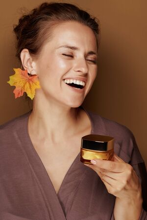 Hello autumn. Portrait of smiling modern middle age woman in a bathrobe with autumn leaf earring holding facial creme against bronze background.