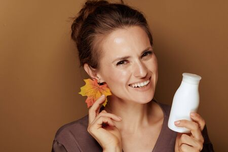 Hello autumn. Portrait of happy elegant 40 year old woman in a bathrobe with autumn leaf earring holding face cleansing milk isolated on beige background.