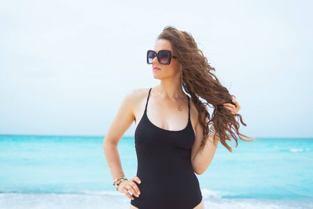 modern middle age woman in sunglasses and with long curly hair in elegant black bathing suit on a white beach looking into the distance.